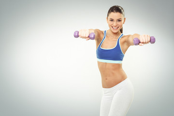 Fototapeta Beautiful young woman exercise with dumbbells on white backgroun