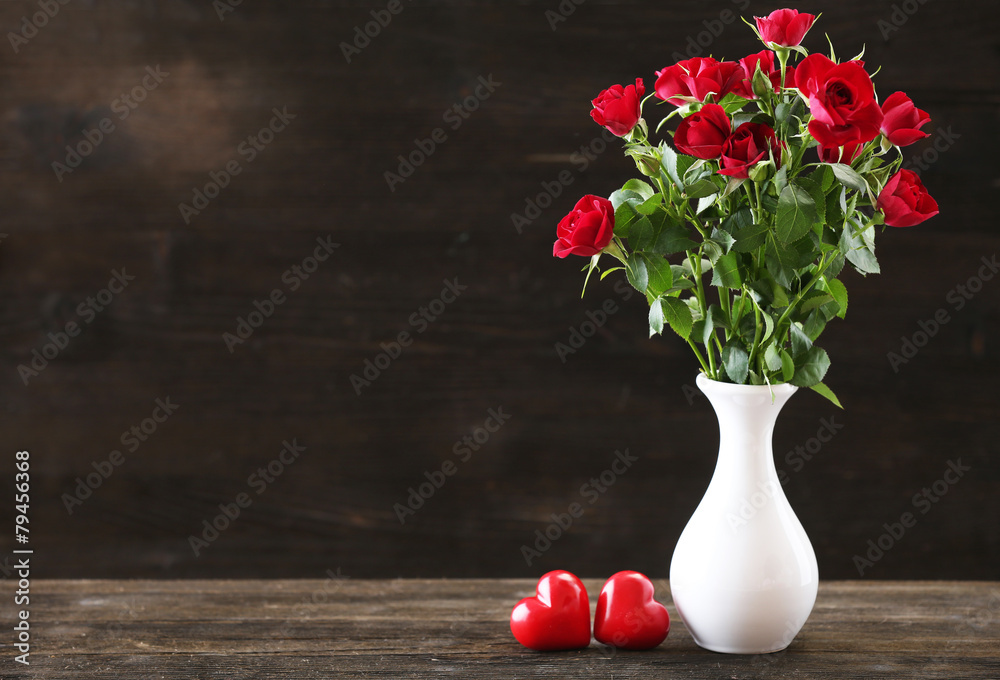 Bouquet of red roses in white vase with hearts