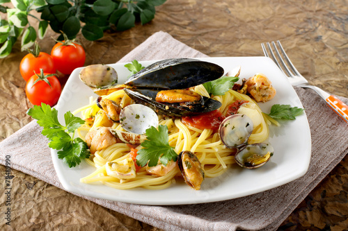 Fotografering  Spaghetti with salmon, clams and mussels