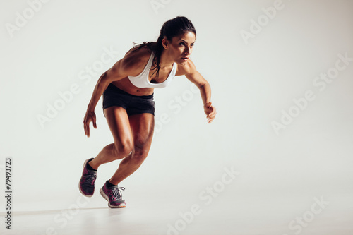 Fotomural  Young woman starting to run and accelerating