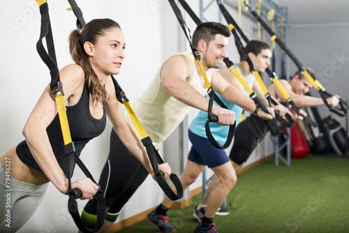 Ludzie na siłowni wykonujący ćwiczenia z elastycznej liny trx