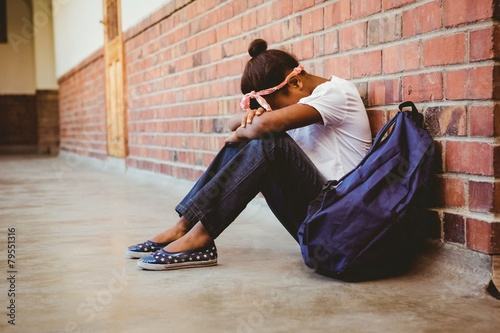 Foto op Plexiglas Wand Tensed girl sitting against brick wall in school corridor