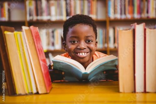 Fotografiet Cute boy reading book in library