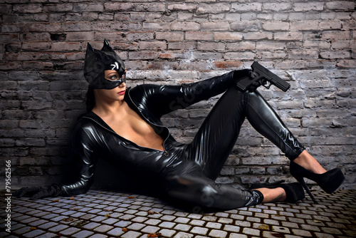 Sexy female in black catwoman costume with gun Fotobehang