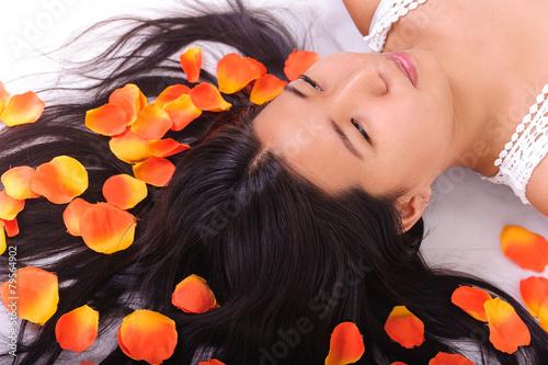Photo  Oriental girl posing in studio lying among petals