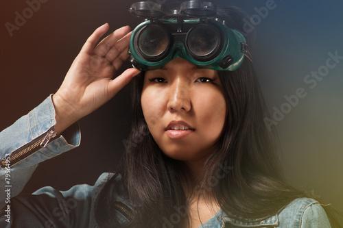 Oriental girl posing in studio with wleding goggles Canvas Print