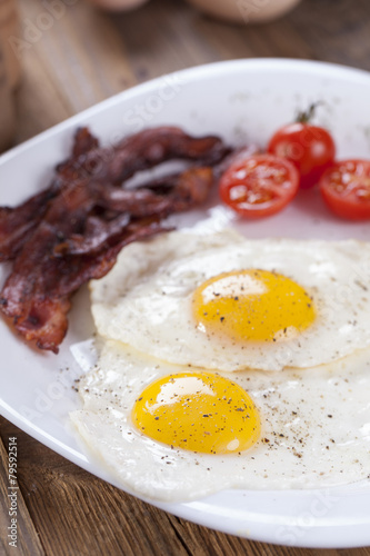 Foto op Plexiglas Gebakken Eieren Fried egg and bacon on a plate with spices and vegetables