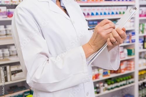 In de dag Apotheek Pharmacist writing prescription on clipboard