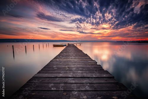 Magnificent lake sunset with boats and a wooden pier