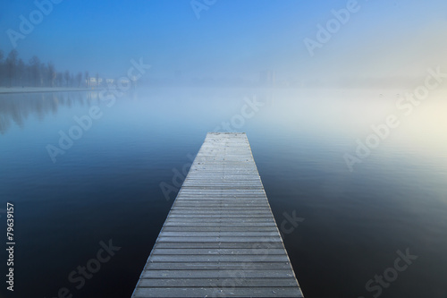 Empty jetty in a foggy lake during sunrise.