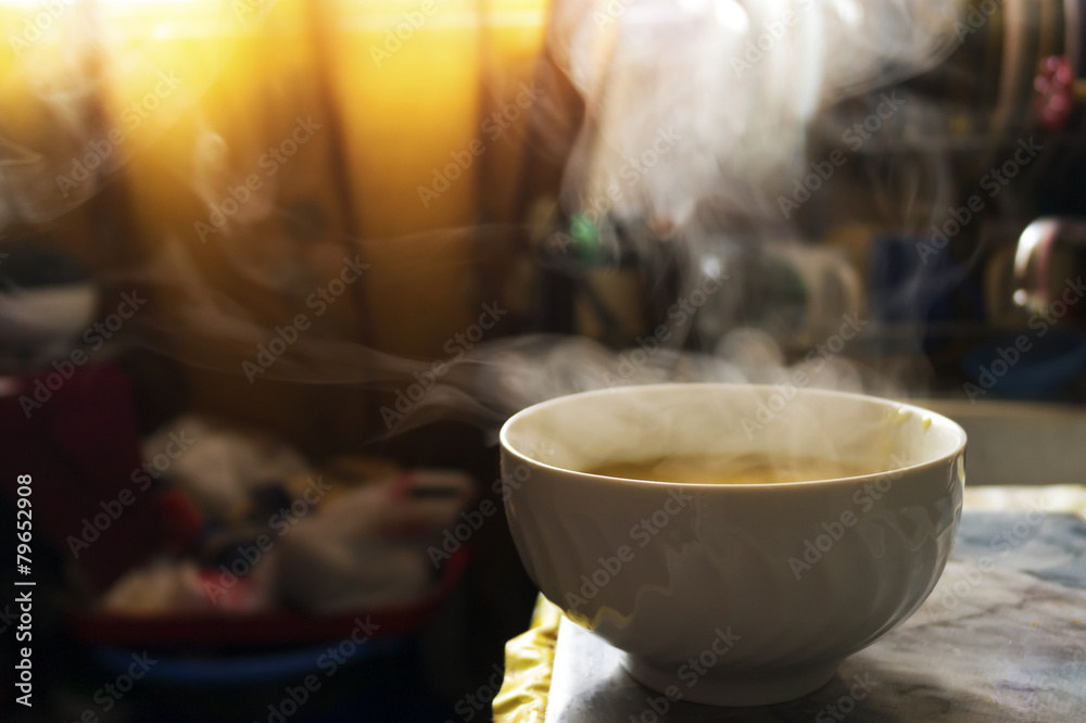 Fototapeta Steaming hot soup in a bowl in the kitchen under warm sunlight