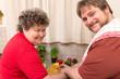 Geistig behinderte Frau und junger Mann schneiden gemeinsam Gem