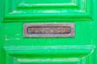Leinwanddruck Bild - A letter box in a green old wooden door