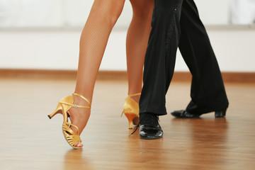 Fototapeta Beautiful womanish and masculine legs in active ballroom dance,