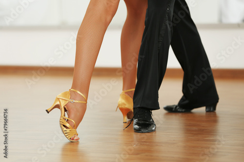 Beautiful womanish and masculine legs in active ballroom dance,