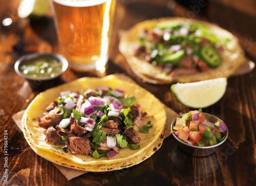 authentic mexican tacos with beer on wooden table