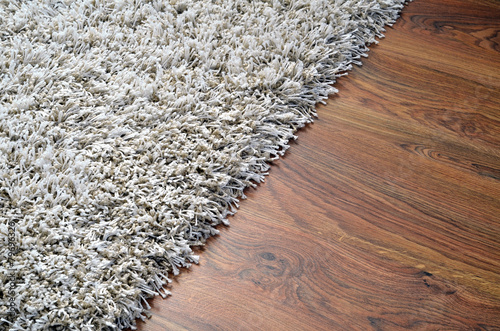 Fototapeta White shaggy carpet on brown wooden floor