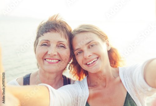 Obraz mother and adult daughter are doing Selfe on the beach - fototapety do salonu