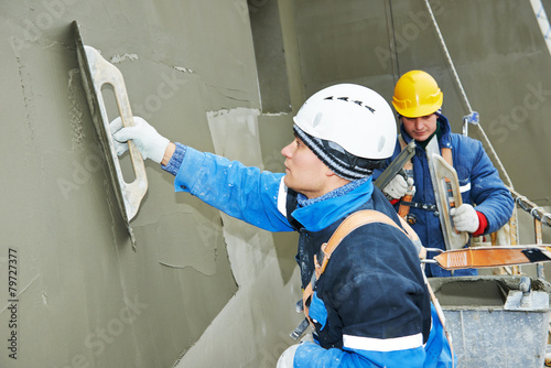 workers at plastering facade work