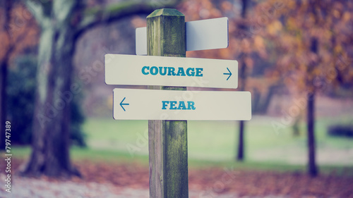 Rustic wooden sign in an autumn park with the words Courage - Fe Fototapet