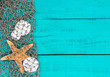 Blank teal blue sign with starfish and sand dollars in fish net border