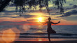 Woman practicing yoga on the beach at amazing sunset.