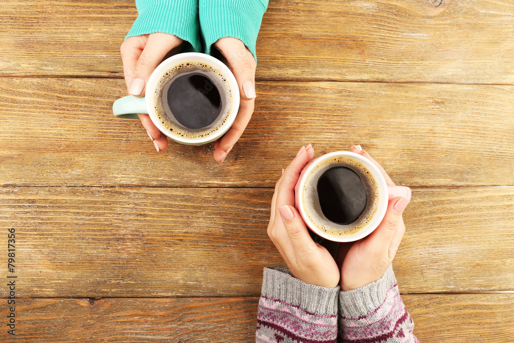 Female hands holding cups of coffee