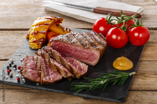 Deurstickers Steakhouse grilled beef steak rare sliced with vegetables