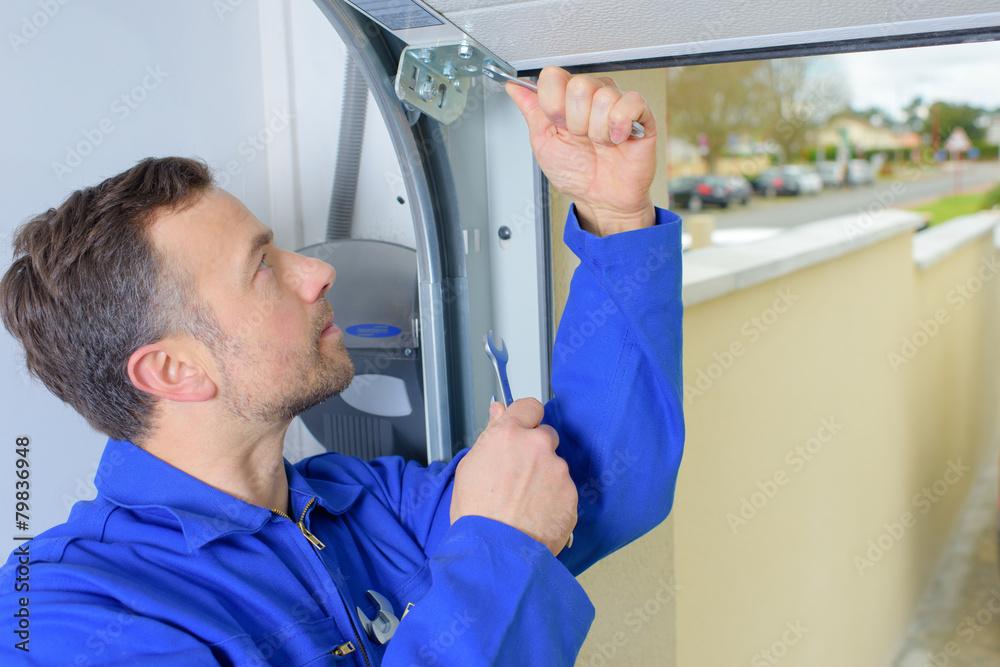Obrazy na płótnie i fototapety na ścianę: Man installing a garage door