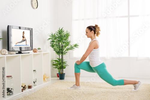 Fotografia  Młoda kobieta robi ćwiczenia rozciągające