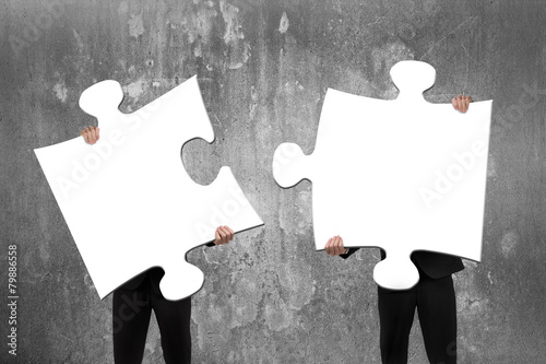 Fotografia, Obraz Two business people assembling white jigsaw puzzles with concret