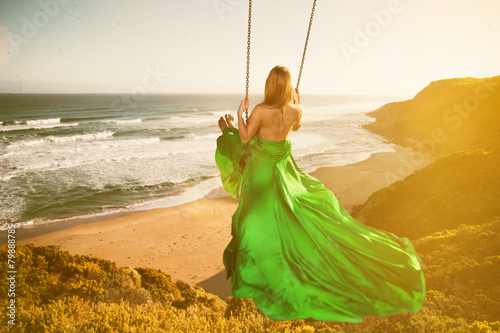 Woman on a swing above the beach