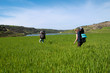 Men and girl with backpacks in deep green grass near sea