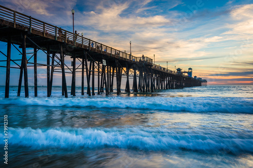 Fototapeten The pier and waves in the Pacific Ocean at sunset, in Oceanside,