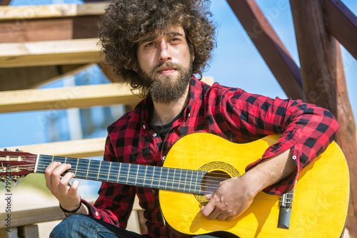 Photo  Guitarist with plaid shirt and afro hair