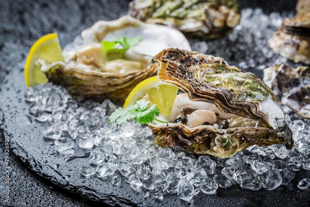 Fototapeta Tasty oysters on ice with lemon
