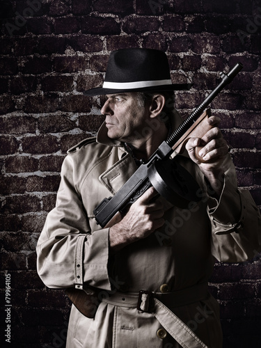 Fotografie, Obraz  Gangster with a gun, wearing raincoat