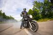 biker staying with unknown big chopper bike on road with smoke o