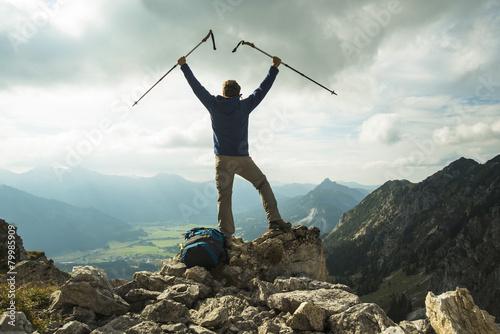 Österreich, Tirol, Tannheimer Tal, junger Mann mit Wanderstöcken jubelt auf Berg