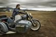 Mann mit Vollbart fährt Motorrad mit Beiwagen