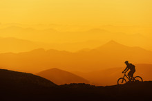 Biker Riding On Mountain Silhouettes Background