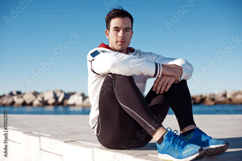 Fotografía  handsome athlete with armband relaxing after fitness outdoors