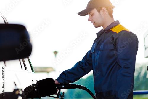 Fotografie, Obraz  Gas station worker refilling car at service station