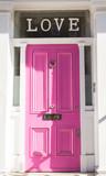 """Jasnoróżowe drzwi na białej ścianie z napisem """"Miłość"""" - 80036549"""