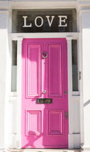 "Bright Pink Door On A White Wall With The Writing ""Love"""