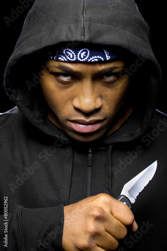 Fototapeta  thug holding a knife coming out of the shadows