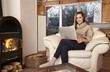Junge Frau zuhause im Sessel mit Laptop