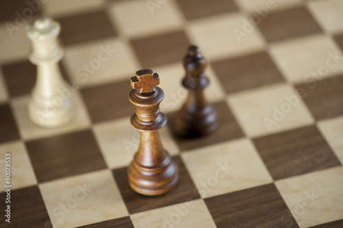 Fotografia, Obraz  Chess pieces and game board background; focus on king