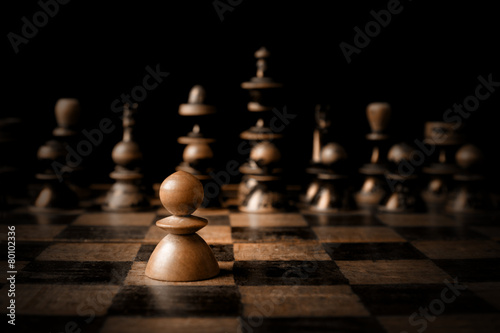 Chess. White pawn against all black. Wallpaper Mural