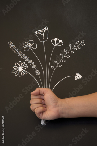 Fototapeta holding flowers on blackboard obraz na płótnie